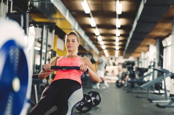 Jeune femme faisant des exercices avec un rameur